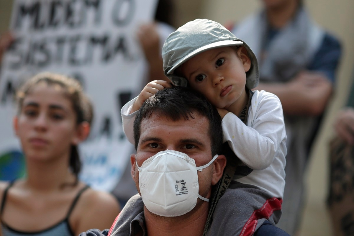 A father with his son attends a global protest on climate change in Rio de Janeiro. (AP Photo/Silvia Izquierdo)
