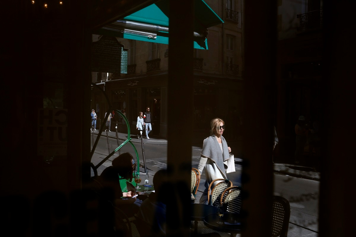 A woman walking on the street is reflected in a mirror of the cafe
