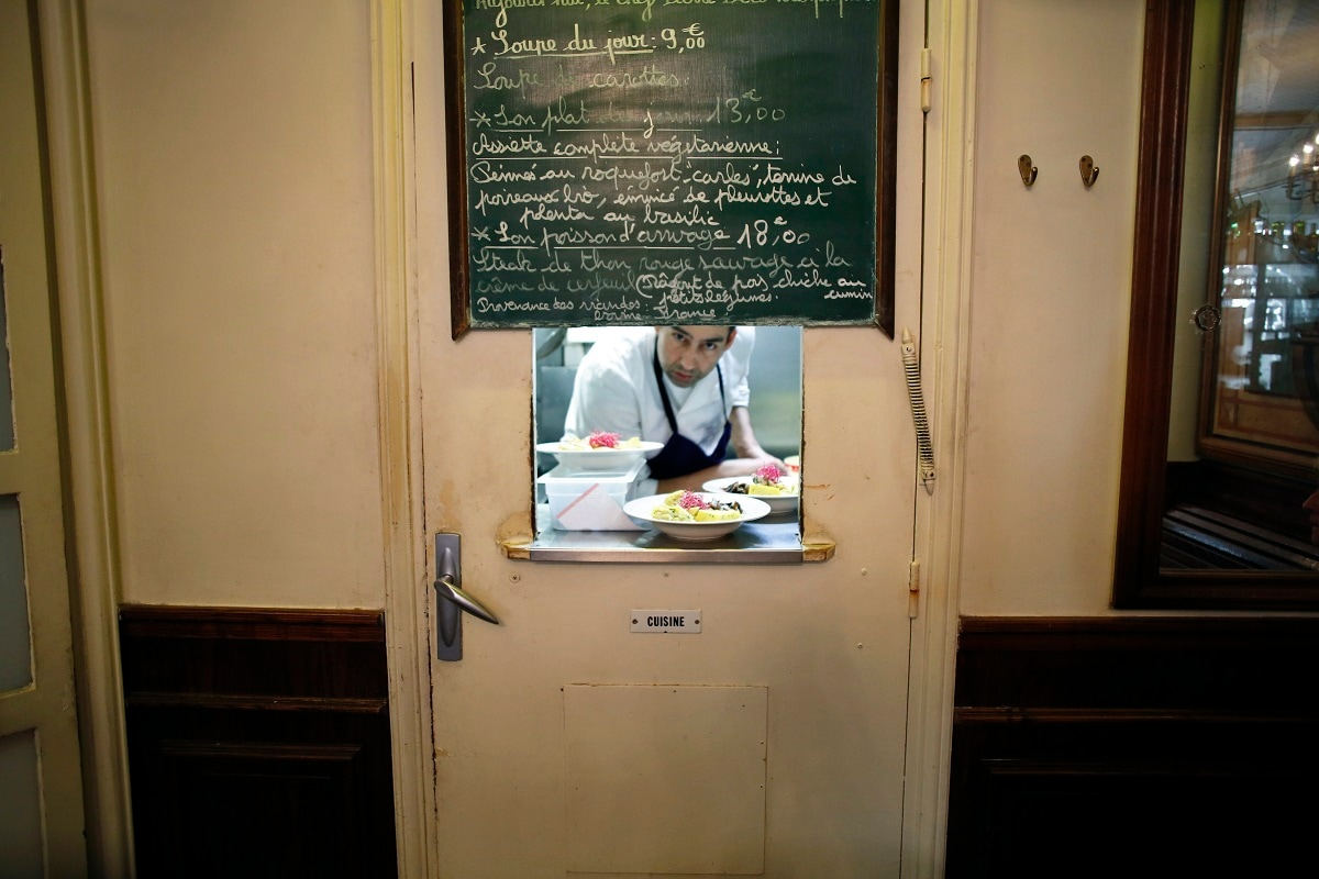 Chef Philippe looks through the window of the kitchen of the cafe