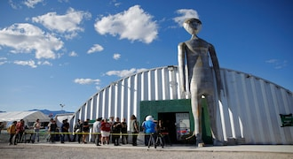 """People line up outside of the gift shop at the Storm Area 51 Basecamp event Friday, Sept. 20, 2019, in Hiko, Nev. The event was inspired by the """"Storm Area 51"""" internet hoax. Thousands of curious Earthlings from around the globe traveled to festivals, and several hundred made forays toward the secret Area 51 military base in the Nevada desert on Friday, drawn by an internet buzz and a social media craze sparked by a summertime Facebook post inviting people to """"Storm Area 51."""" (AP Photo/John Locher)"""