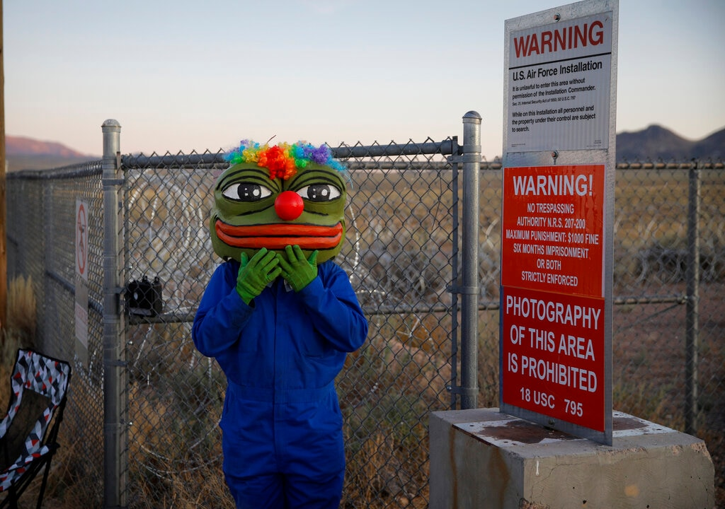 Martin Custodio wears a Pepe mask while standing near razor wire at an entrance to the Nevada Test and Training Range near Area 51, Friday, Sept. 20, 2019, near Rachel, Nev. People came to visit the gate inspired by the
