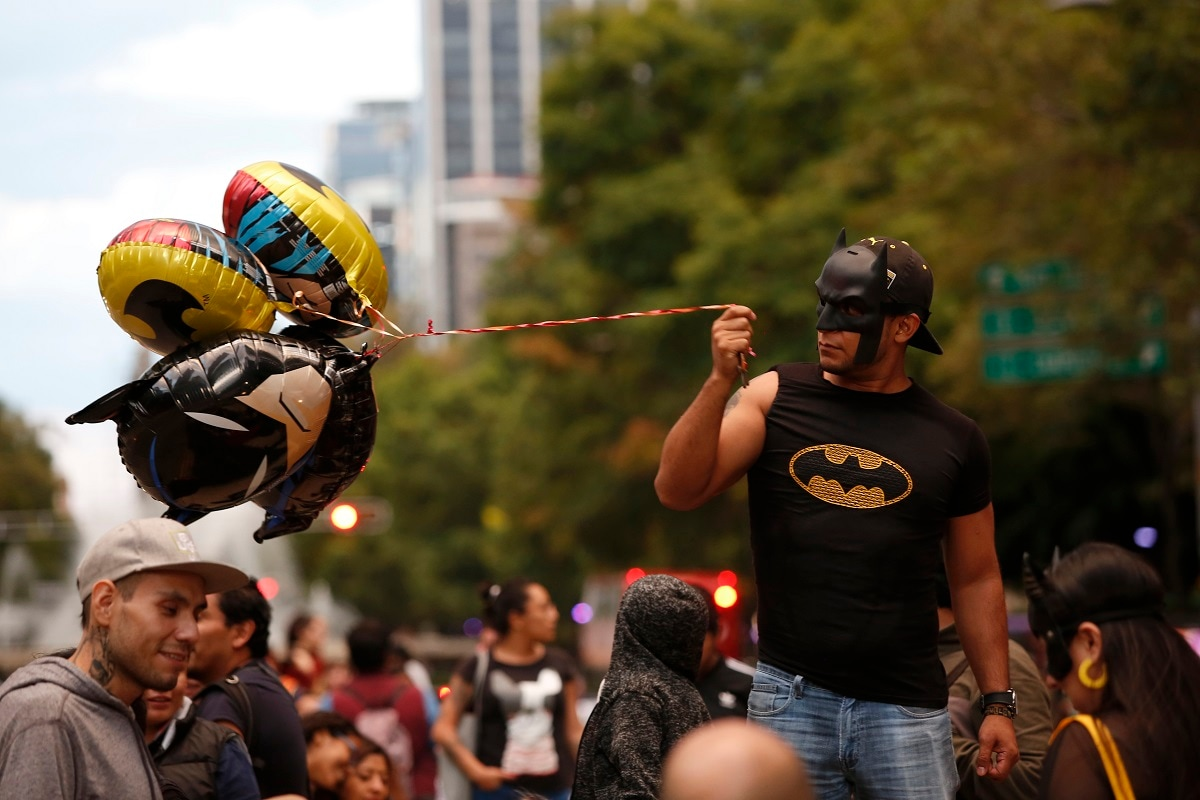 A man holds Batman balloons before the Bat-signal lighting during the commemorating of Batman's 80th anniversary in Mexico City. (AP Photo/Ginnette Riquelme)