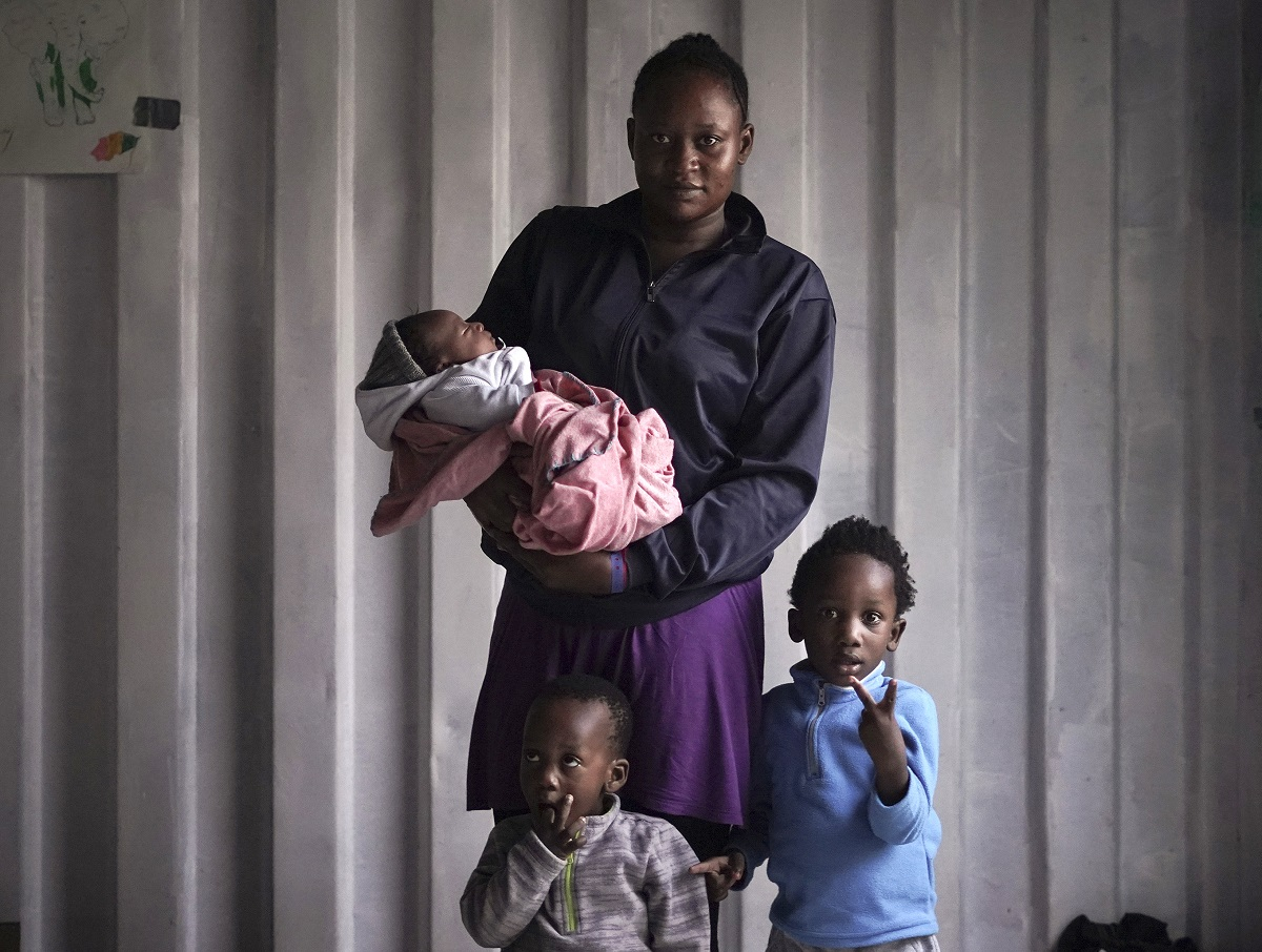 "Prudence Aimee, 30, from Cameroon poses for a photo with her children from left to right Ange, Wifrid,1, and William, 3. Prudence gave birth to her third son Sept. 13, just three days before boarding an overcrowded wooden boat in the hope of getting her children out of war-torn Libya. Her husband was not able to join them and stayed behind. Her eldest son William was very excited to arrive in Italy and waved at every boat that passed by while saying ""Hey! Hey! Hey!"" (AP Photo/Renata Brito)"