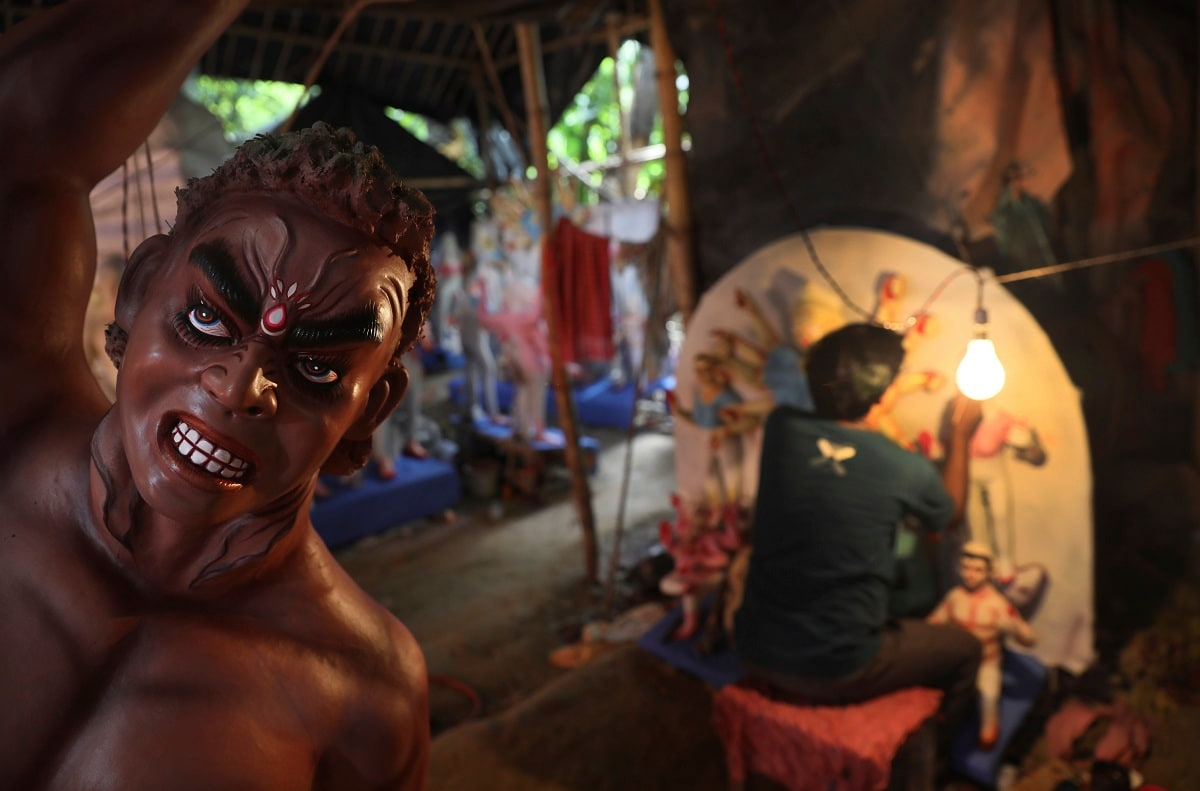 An artisan paints a clay idol of Durga at a makeshift studio in New Delhi. (AP Photo/Manish Swarup)