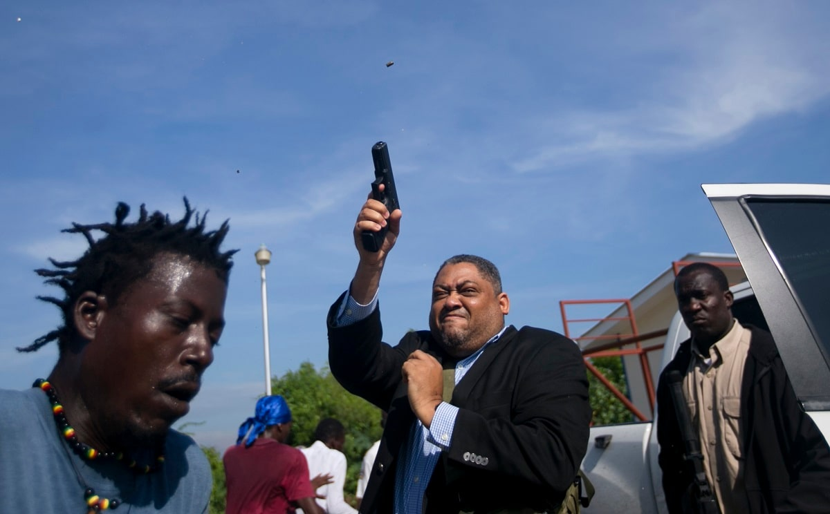 Sen. Ralph Fethiere fires his gun as protesters rush at him and members of his entourage outside the Haitian Senate, in Port-au-Prince, Haiti. Senators were convening Monday to approve the prime minister nomination. Associated Press photographer Dieu Nalio Chery was hit in the jaw by what appeared to be a fragment of one of the bullets fired by Fethiere. (AP Photo/Dieu Nalio Chery)