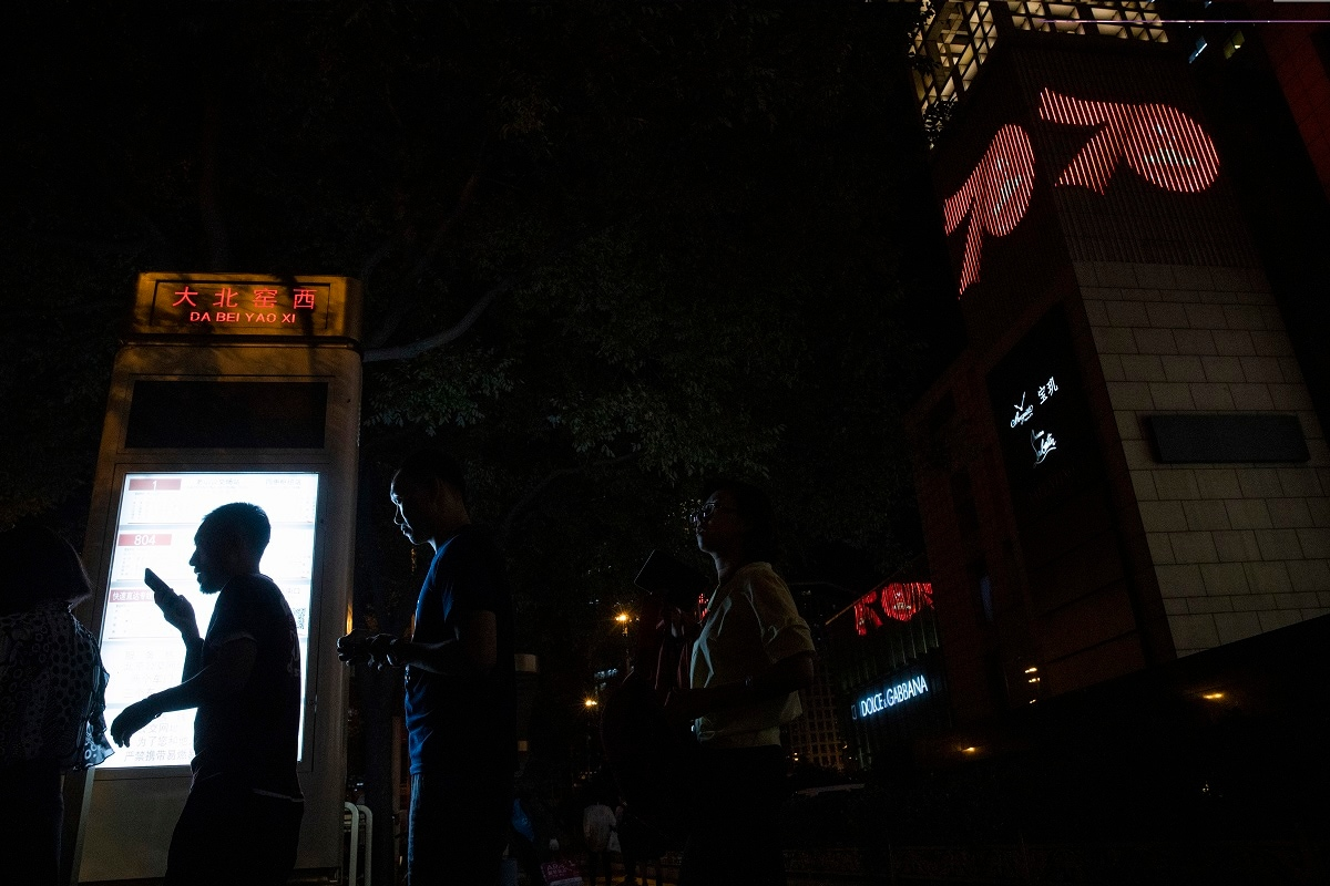 Residents queue up for the bus near light displays on buildings in the Central Business District marking the upcoming 70th anniversary of the Founding of the People's Republic of China in Beijing.(AP Photo/Ng Han Guan)