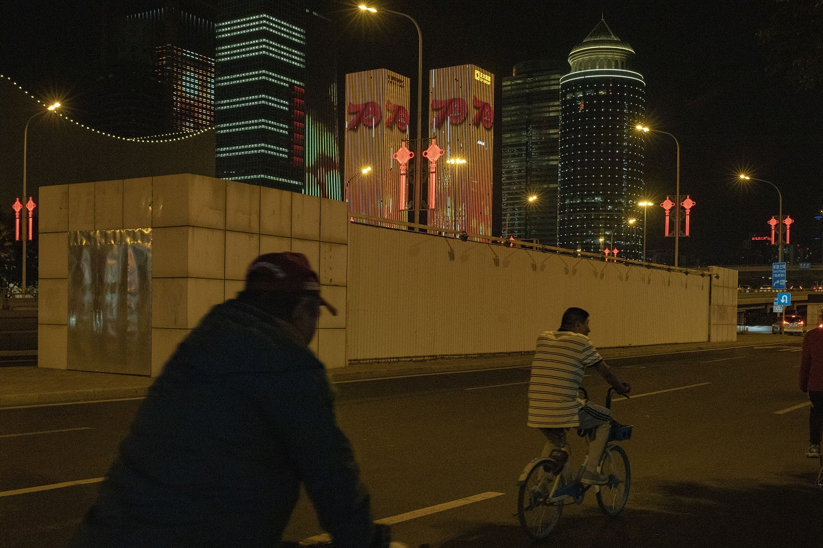 Cyclists pass by building lit up with the number 70 to mark the upcoming 70th anniversary of the Founding of the People's Republic of China in Beijing. (AP Photo/Ng Han Guan)