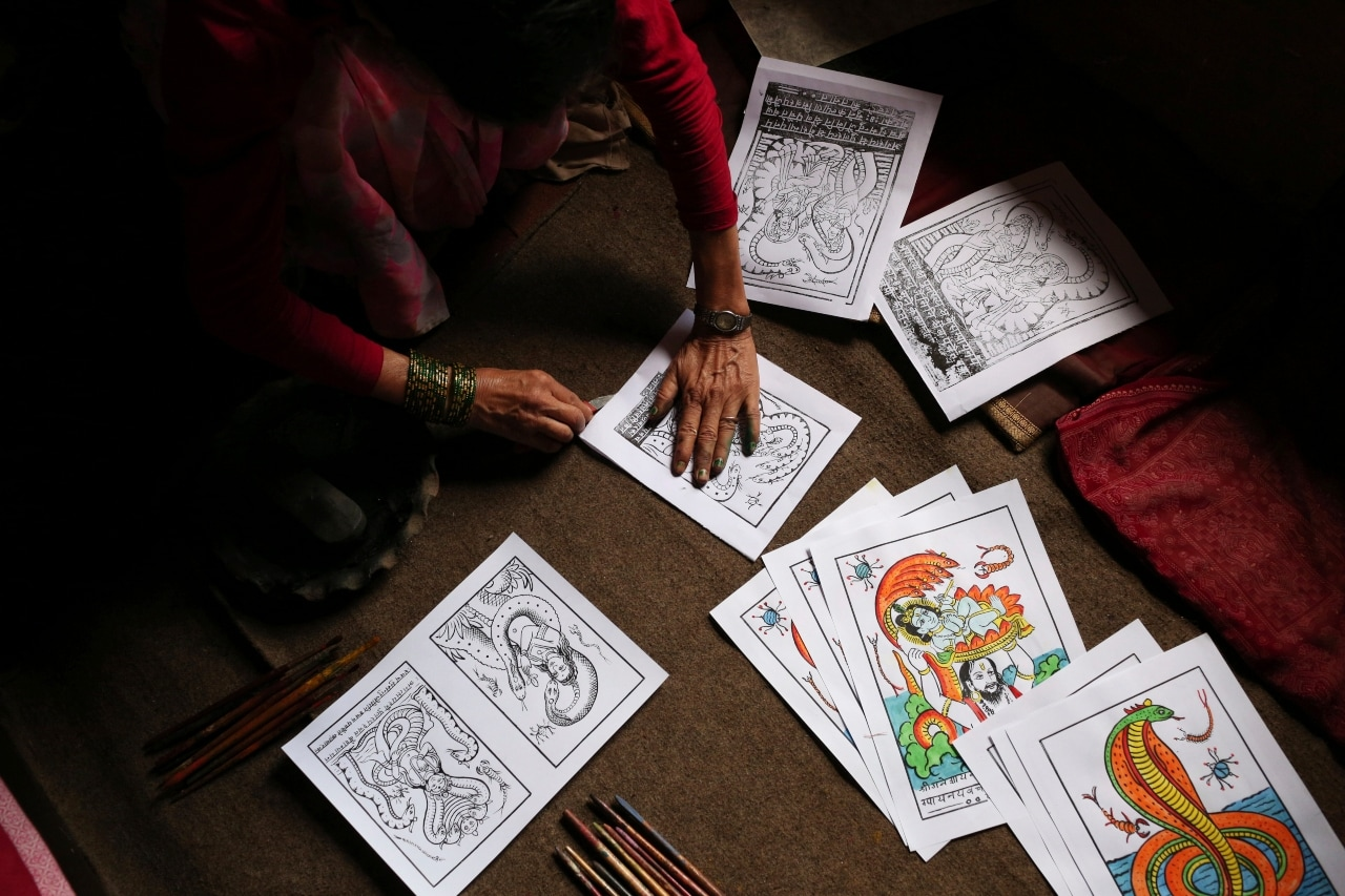 In this July 31, 2019, photo, Tej Kumari Chitrakar makes traditional paintings ahead of Naag Panchami festival at her residence in Bhaktapur, Nepal. Chitrakar families in the Nepalese capital of Kathmandu were renowned traditional painters and sculptors who depicted gods and goddesses on temples, masks of Hindu deities and posters for various religious celebrations. For Tej Kumari and her husband it is a struggle to keep the dying art alive against the modern mass produced prints. (AP Photo/Niranjan Shrestha)