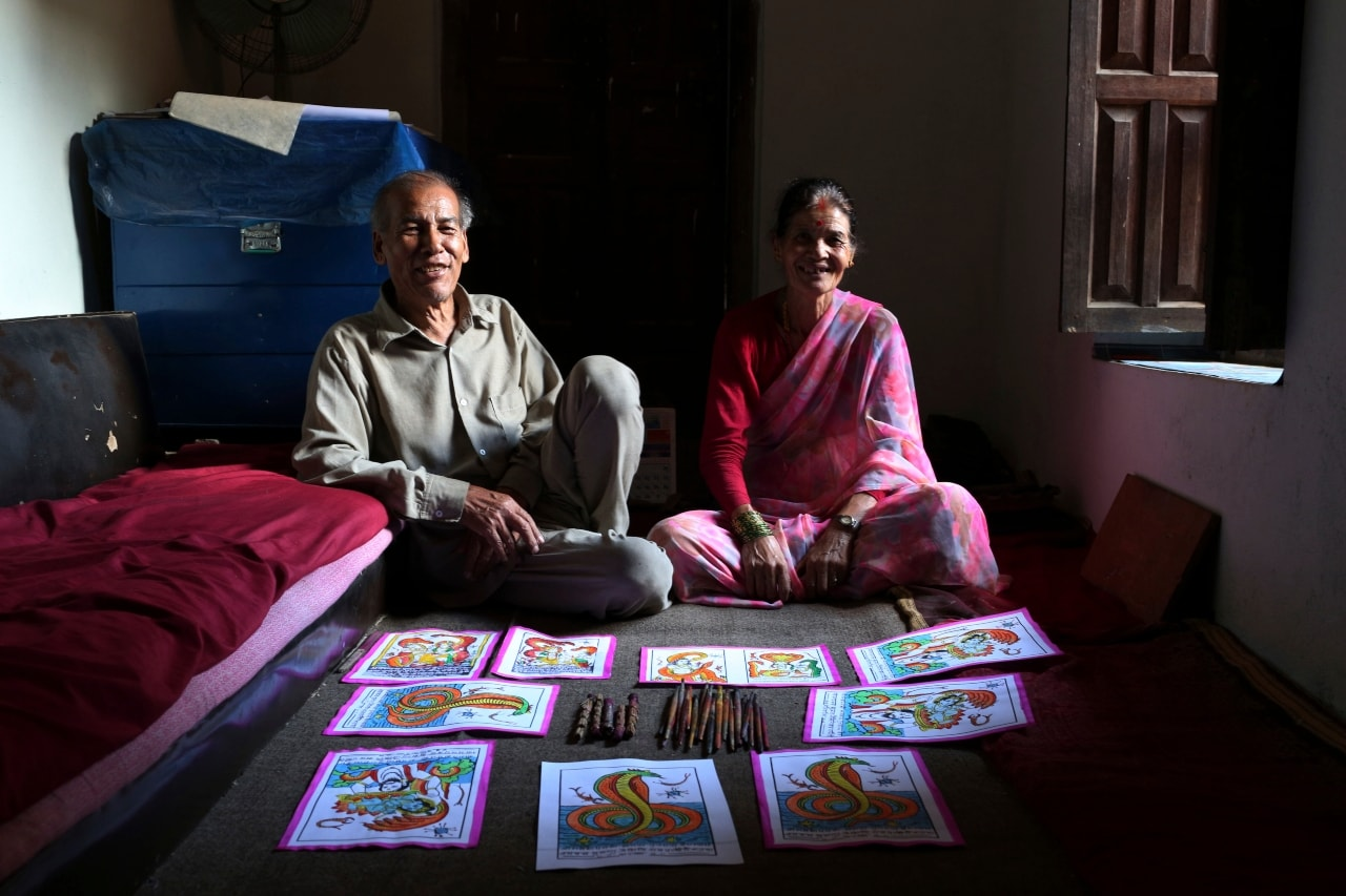 In this July 31, 2019, photo, Chitrakar couple Tej Kumari and Purna, left, pose for photographs at their residence in Bhaktapur, Nepal. Chitrakar families in the Nepalese capital of Kathmandu were renowned traditional painters and sculptors who depicted gods and goddesses on temples, masks of Hindu deities and posters for various religious celebrations. For the Chitrakar couple it is a struggle to keep the dying art alive against the modern mass produced prints. (AP Photo/Niranjan Shrestha)