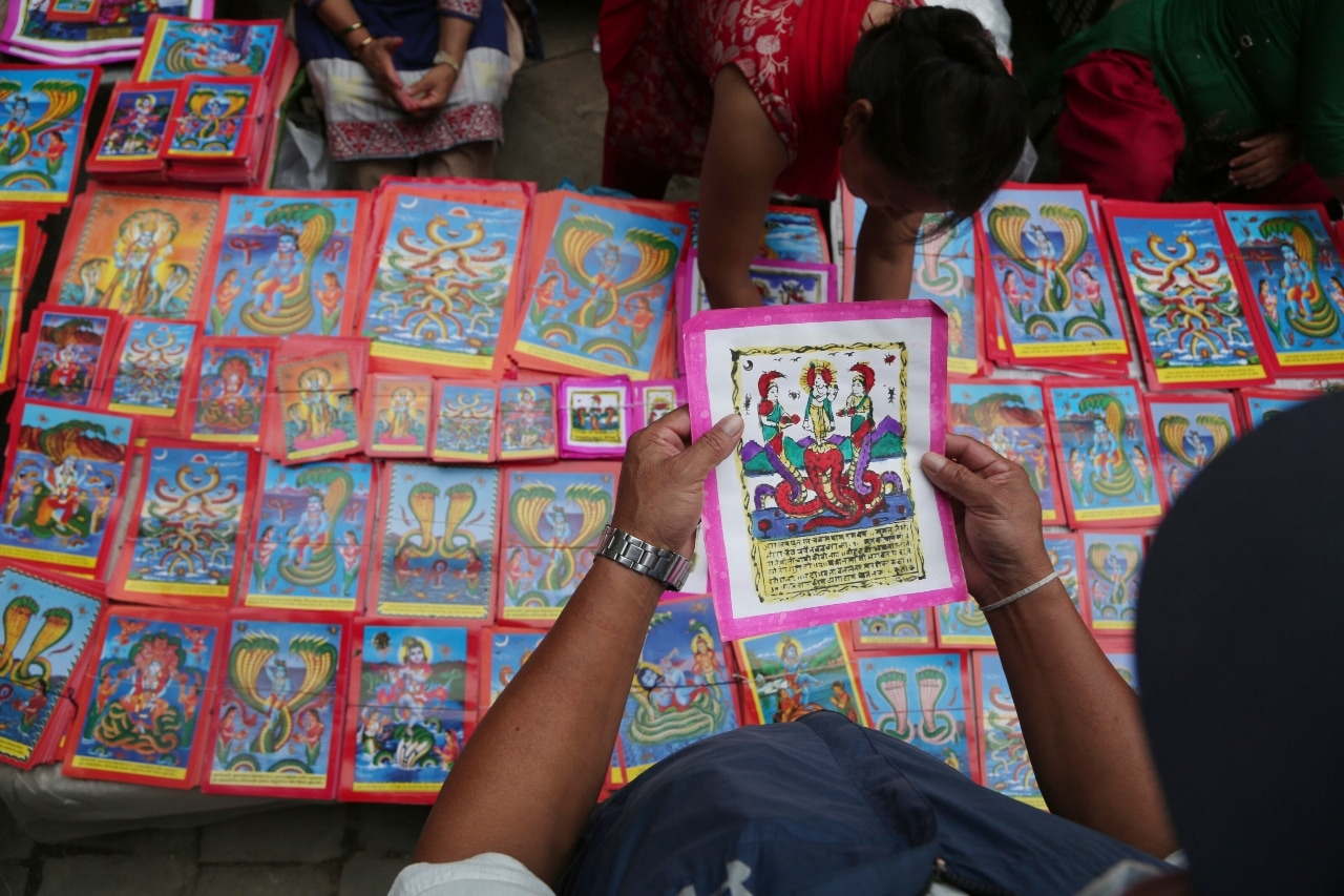 In this Aug. 4, 2019, photo, a Nepalese man checks a traditional painting displayed for sale at a market during Naag Panchami festival in Bhaktapur, Nepal. The art and tradition of Nepal's Chitrakar families, who depicted gods and goddesses on temples, masks of Hindu deities and posters for various religious celebrations is dying because of mass machine printed posters and card-size pictures of gods that are cheaper and more popular. (AP Photo/Niranjan Shrestha)