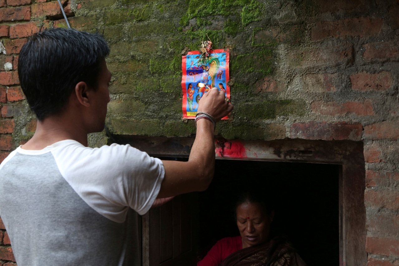 In this Aug. 5, 2019, photo, a Nepalese man displays a machine made painting on his house door during Naag Panchami festival in Bhaktapur, Nepal. The art and tradition of Nepal's Chitrakar families, who depicted gods and goddesses on temples, masks of Hindu deities and posters for various religious celebrations is dying because of mass machine printed posters and card-size pictures of gods that are cheaper and more popular. (AP Photo/Niranjan Shrestha)