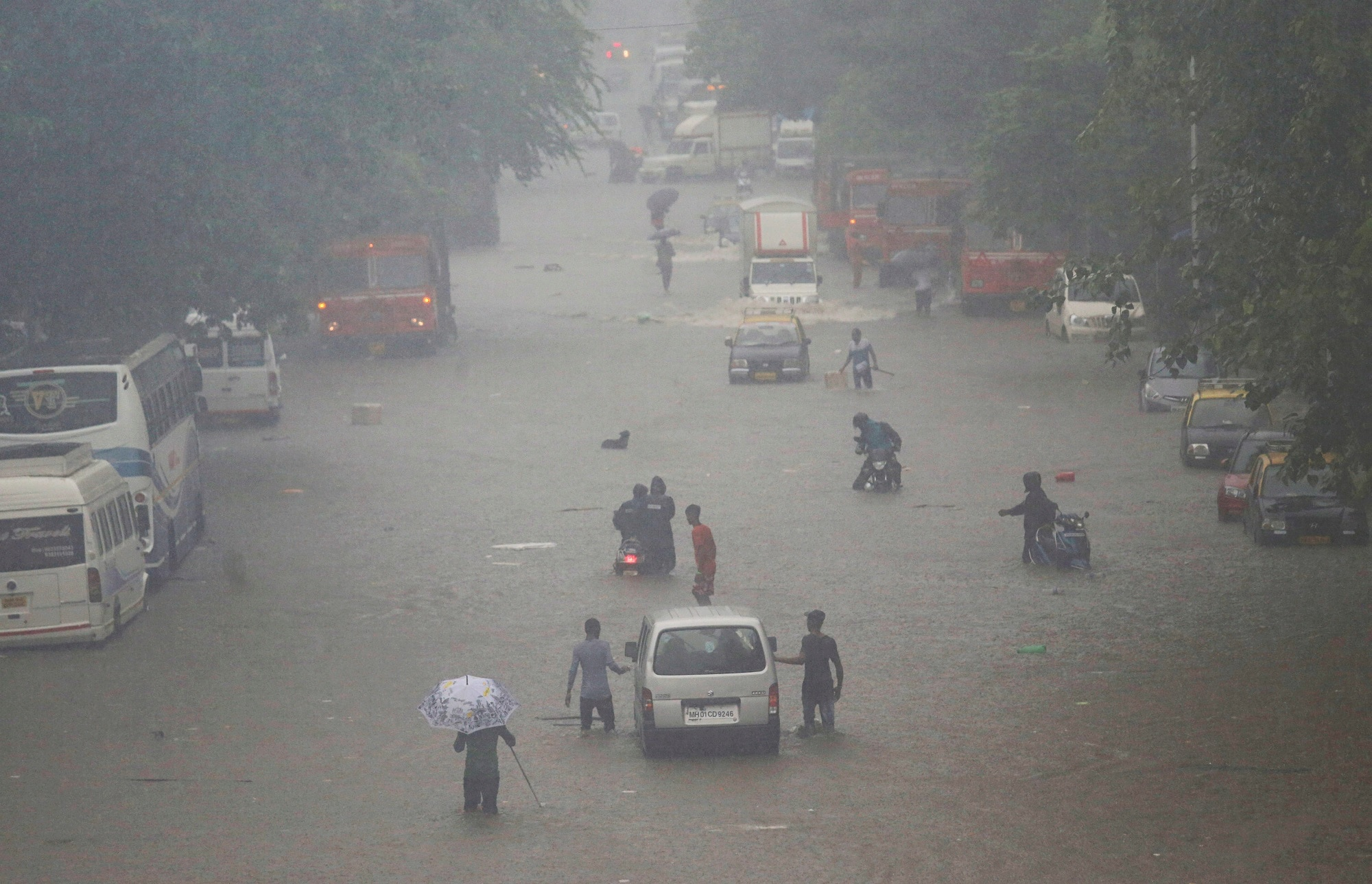 Commuters walk on a flooded street. Photo: Reuters