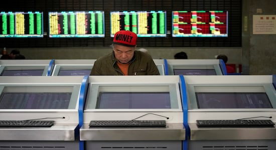 An investor looks at computer screens showing stock information at a brokerage house in Shanghai