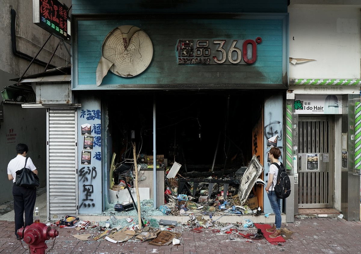 A man inspects a Bestmart store which was vandalised during Sunday's anti-government protest in Hong Kong. Hong Kong's businesses will likely foot the bill for vandalism inflicted over the past four months during the territory's most violent protests in living memory as few of them bought insurance coverage for riot damage, industry insiders said. (REUTERS/Umit Bektas)