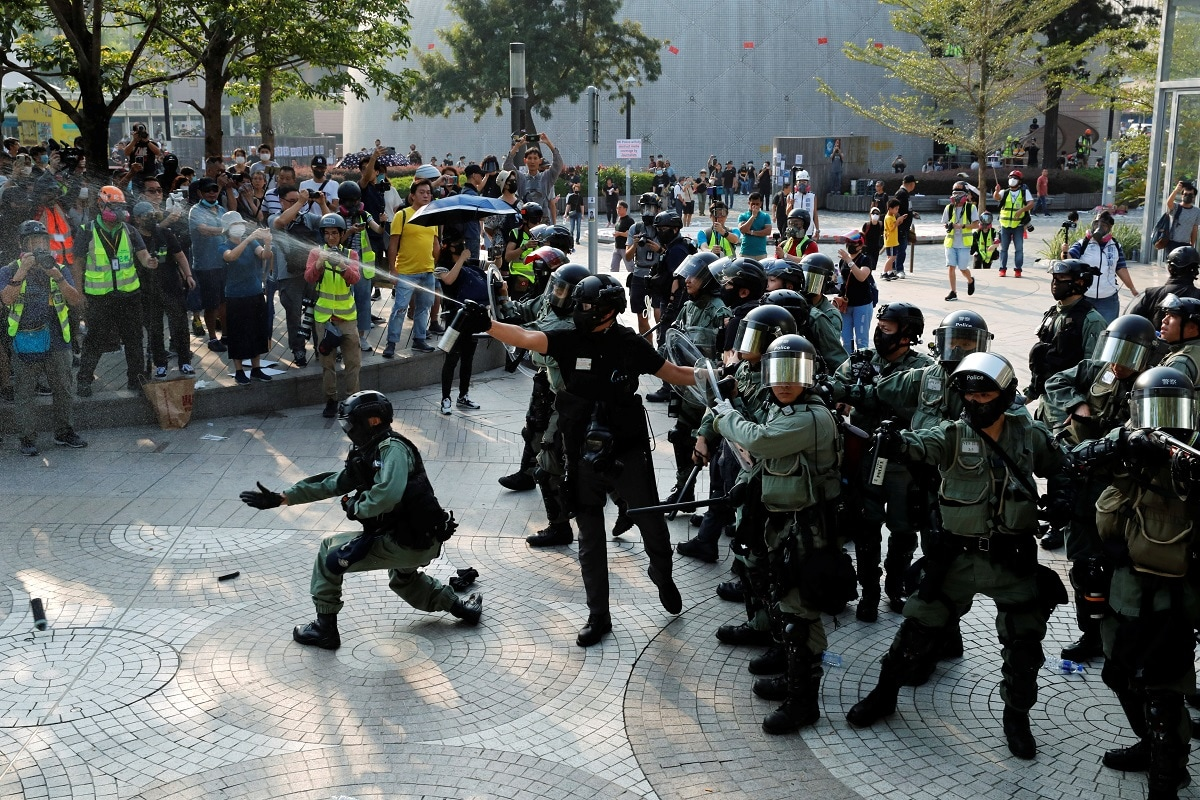 Police officers release pepper spray during an anti-government protest in Hong Kong's tourism district of Tsim Sha Tsui. The number of protesters had grown by the minute, streaming down Nathan Road to the water's edge, facing the dramatic skyline of Hong Kong island opposite, but many fled after the tear gas and pepper spray were fired. REUTERS/Umit Bektas