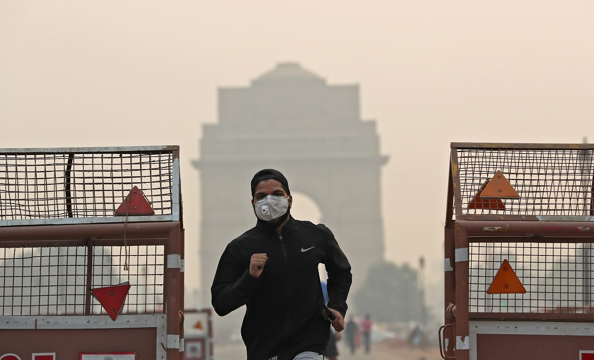 A man wearing a mask runs past the India Gate on a smoggy morning in New Delhi. The Supreme Court had ordered residents to only use safe and environmentally friendly fireworks for a maximum of two hours, and only in designated areas such as parks, but the law was violated in several parts of the city, residents said. REUTERS/Adnan Abidi