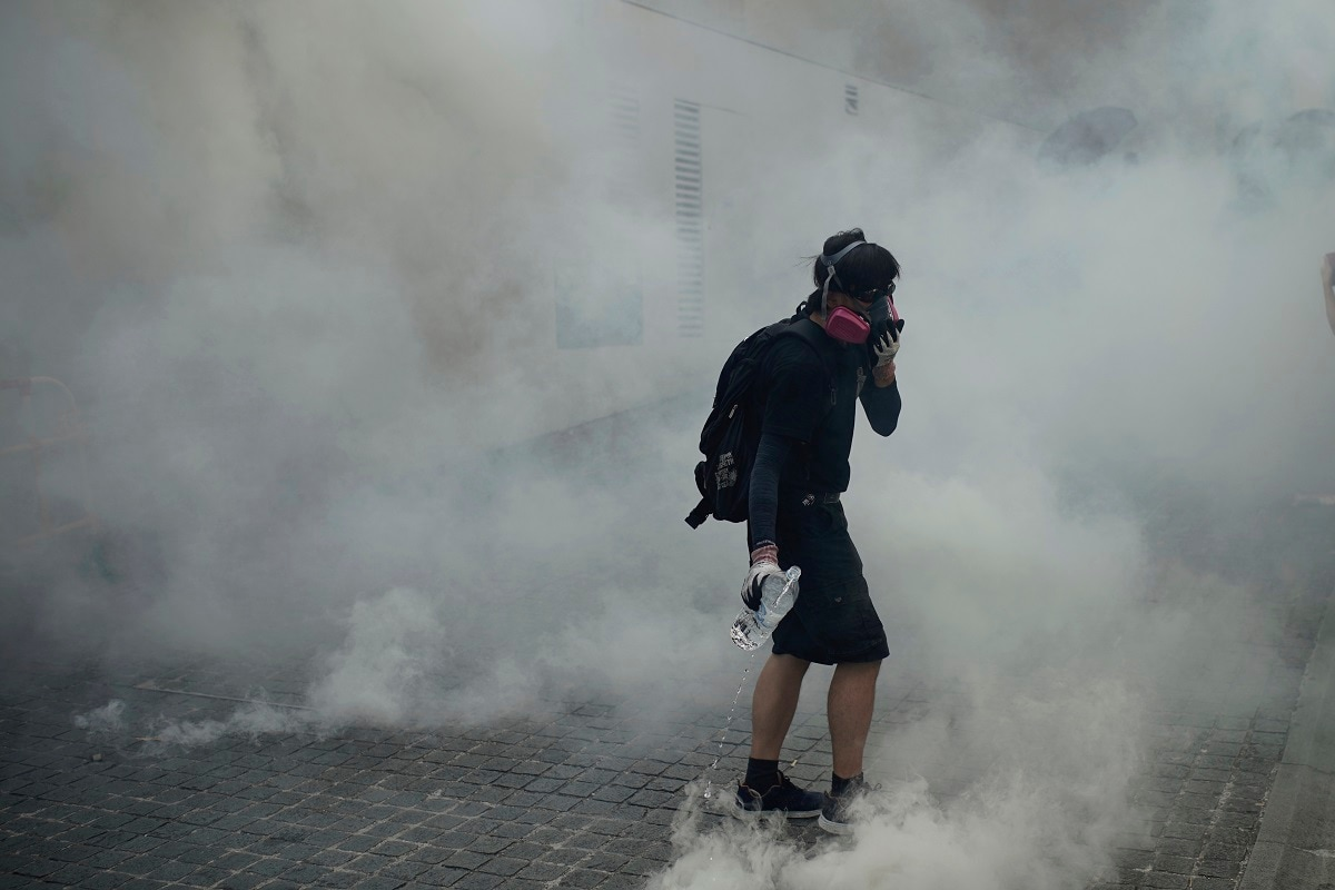 An anti-government protester walks through tear gas smoke during a clash with police at the Wong Tai Sin area in Hong Kong. Thousands of black-clad pro-democracy protesters defied a police ban and marched in central Hong Kong on Tuesday, urging China's Communist Party to