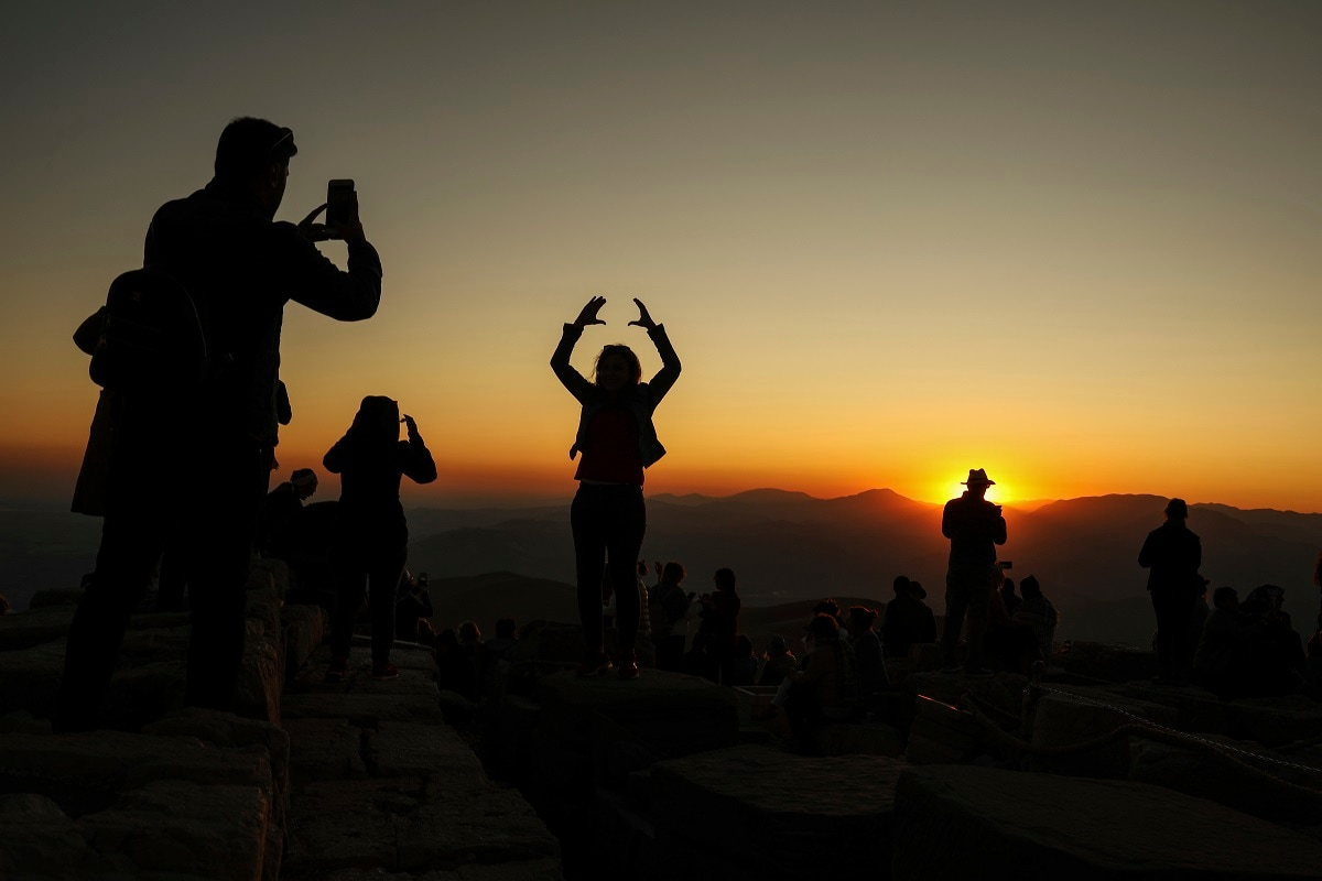 Tourists take pictures at sunset at the archaeological site of Mount Nemrut in Adiyaman, southeastern Turkey, a UNESCO World Heritage Site since 1987. (AP Photo/Emrah Gurel)