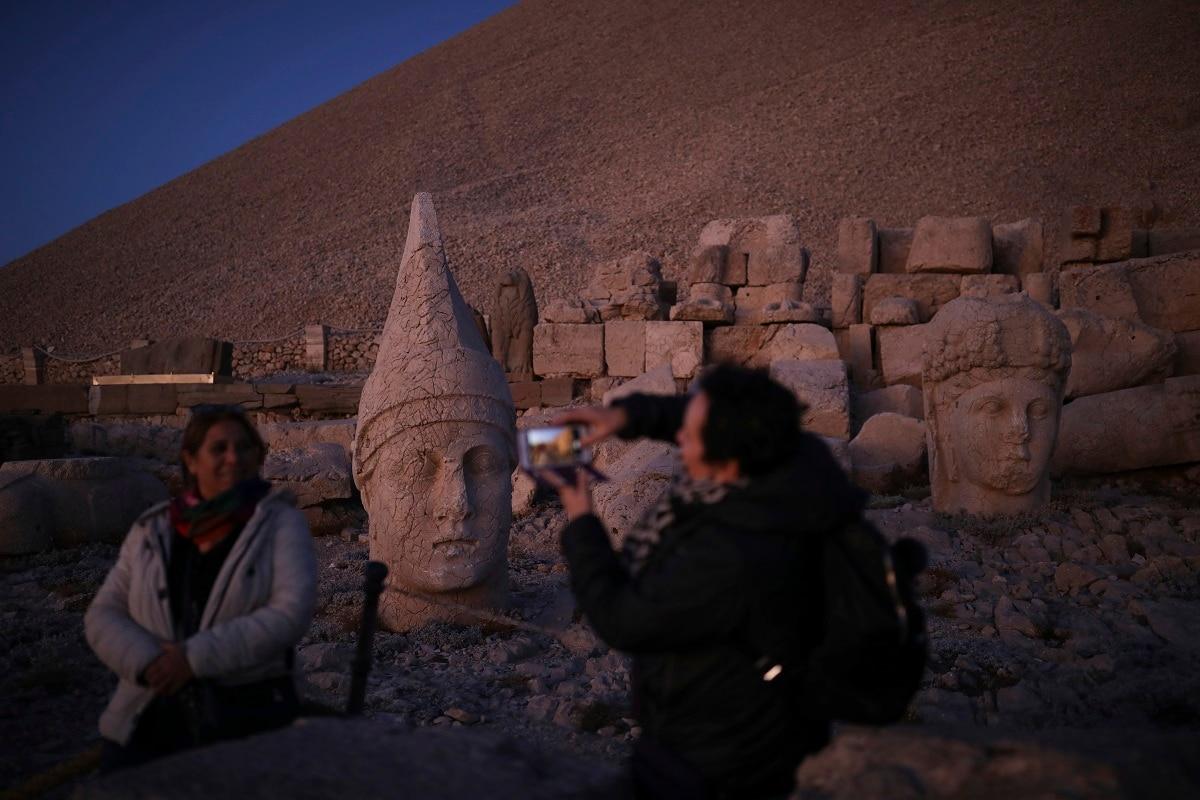 Tourists take photos at the archaeological site of Mount Nemrut in Adiyaman, southeastern Turkey, a UNESCO World Heritage Site since 1987. (AP Photo/Emrah Gurel)