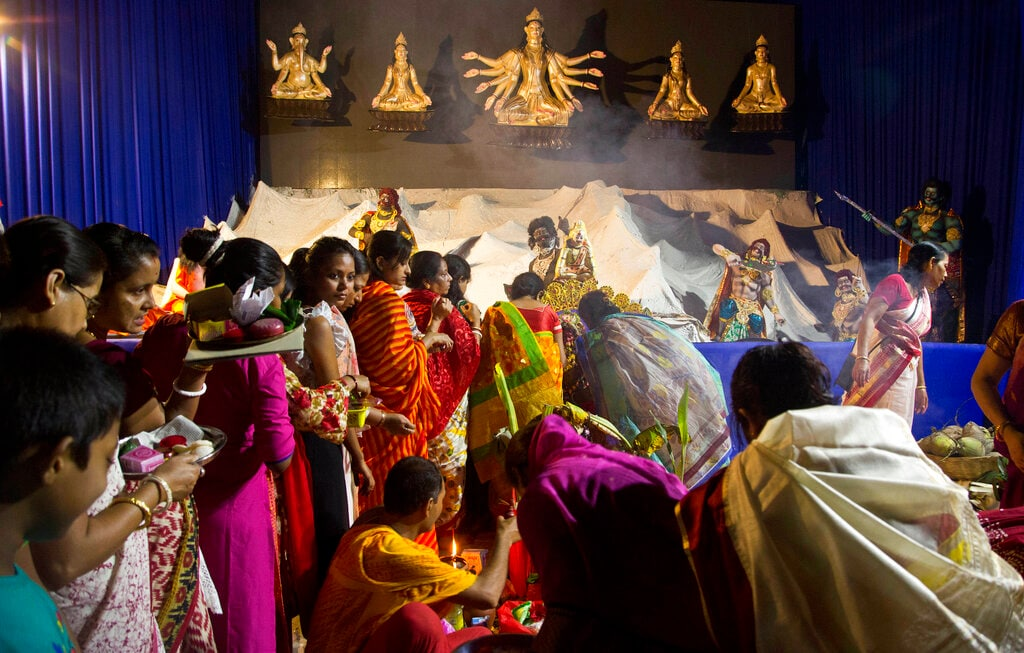 Hindu devotees offer prayers before immersion of Durga idol on the last day of Durga Puja festivities in Gauhati on Tuesday. The festival commemorates the slaying of a demon king by lion-riding, 10-armed goddess Durga, marking the triumph of good over evil. (AP Photo/Anupam Nath)