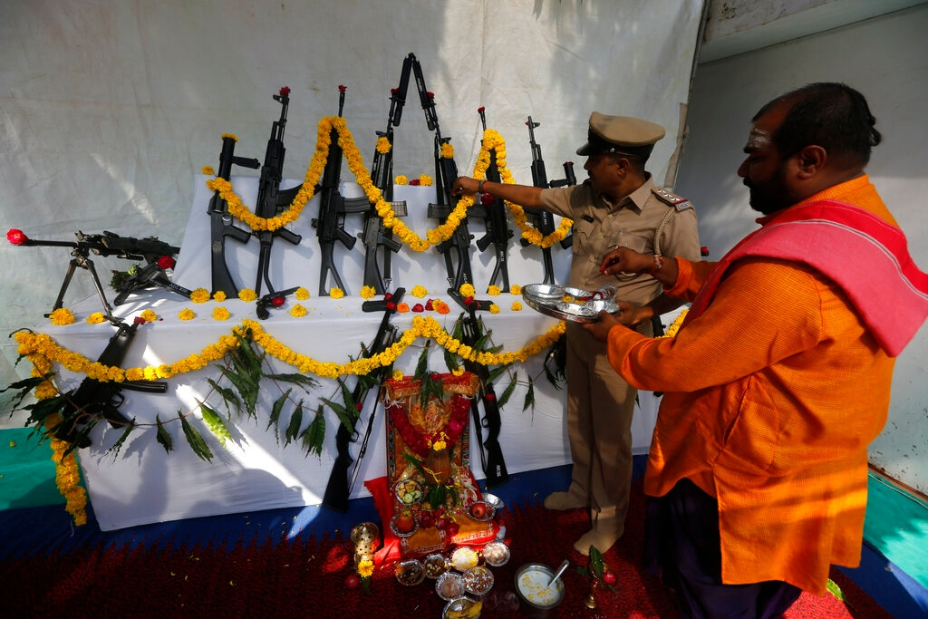 An Indian police officer worships weapons at police headquarters on Vijayadashmi, or Dussehra festival, in Ahmadabad on Tuesday. The festival culminates with the burning of effigies of Ravana, signifying the victory of good over evil. Weapons are also worshipped on this day. (AP Photo/Ajit Solanki)