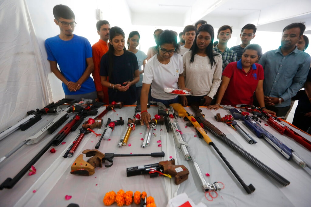People worship weapons at rifle club on Vijayadashmi, or Dussehra festival, in Ahmadabad, India, Tuesday, Oct. 8, 2019. The festival culminates with the burning of effigies of Ravana, signifying the victory of good over evil. Weapons are also worshipped on this day. (AP Photo/Ajit Solanki)