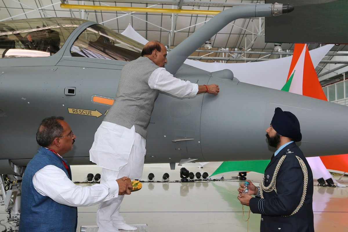 Defense Minister Rajnath Singh writes onto a Rafale jet fighter as a ritual gesture during the handover ceremony at the Dassault Aviation plant in Merignac. (AP Photo/Bob Edme)