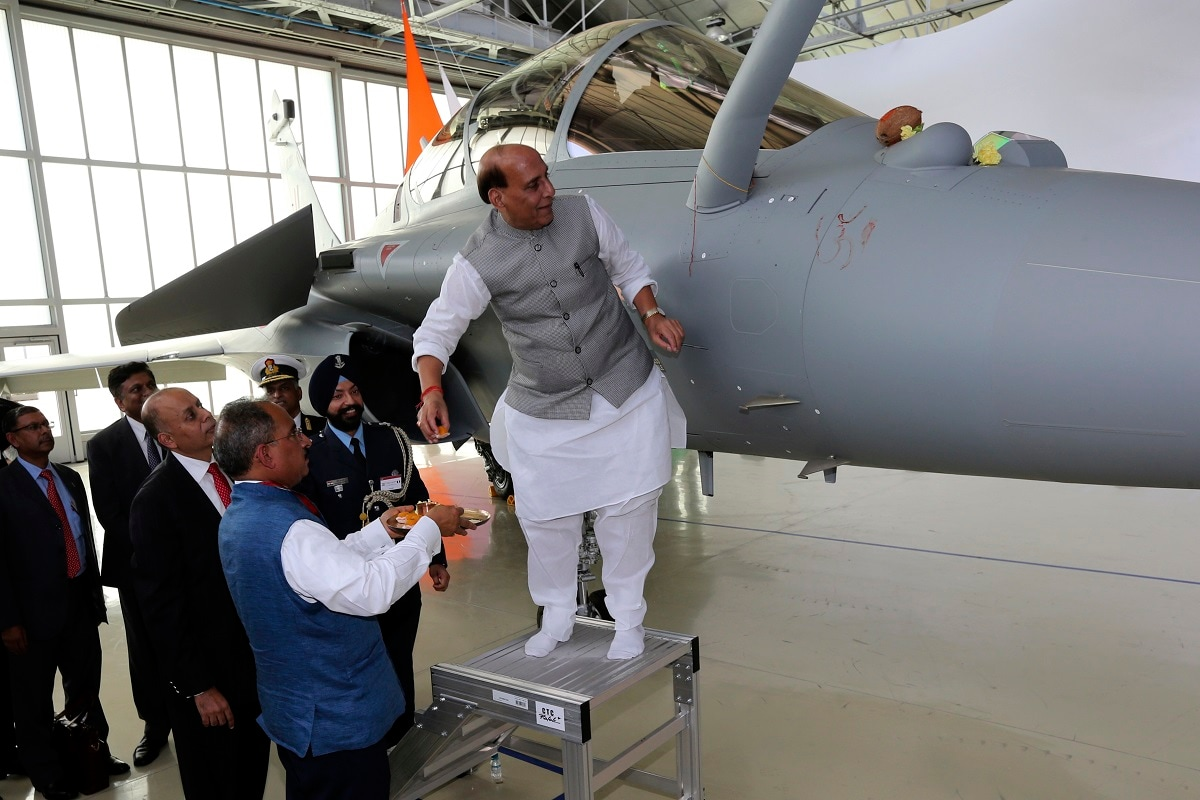 Defense Minister Rajnath Singh has a ritual gesture onto a Rafale jet fighter during the handover ceremony. (AP Photo/Bob Edme)