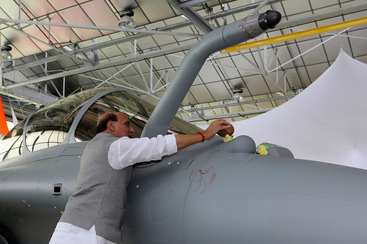 Minister Rajnath Singh puts some flowers as a ritual gesture on a Rafale jet fighter during the handover ceremony. (AP Photo/Bob Edme)