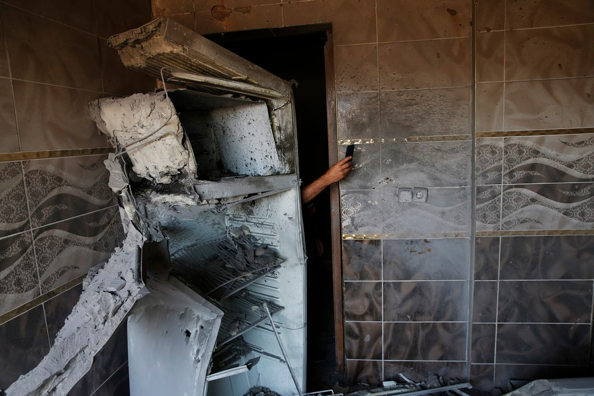 A local resident uses his mobile to take photos of the damages on a house, caused by a mortar fired from inside Syria, on the Turkish town of Akcakale. Nobody got hurt by the attack. The owners of the house weren't home at the time of the attack. Turkey says its military offensive has taken central Ras al-Ayn, a key border town in northeastern Syria, and its most significant gain since its cross-border operation began against Syrian Kurdish fighters began. (AP Photo/Lefteris Pitarakis)