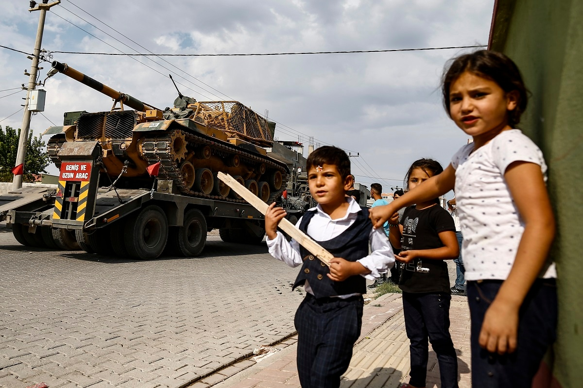 Children watch as army tanks are transported on trucks in the outskirts of the town of Akcakale, in Sanliurfa province. (AP Photo/Emrah Gurel)