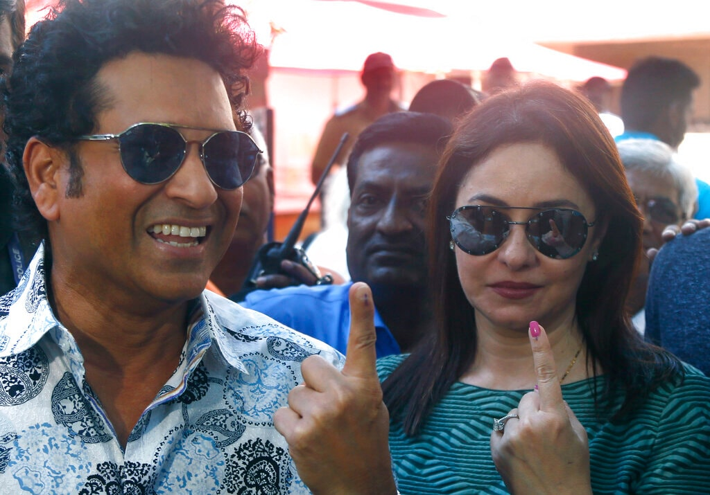 Former Indian cricketer Sachin Tendulkar, left, with his wife Anjali pose for media after casting their votes in Mumbai, India, Monday, Oct. 21, 2019. (AP Photo/Rafiq Maqbool)