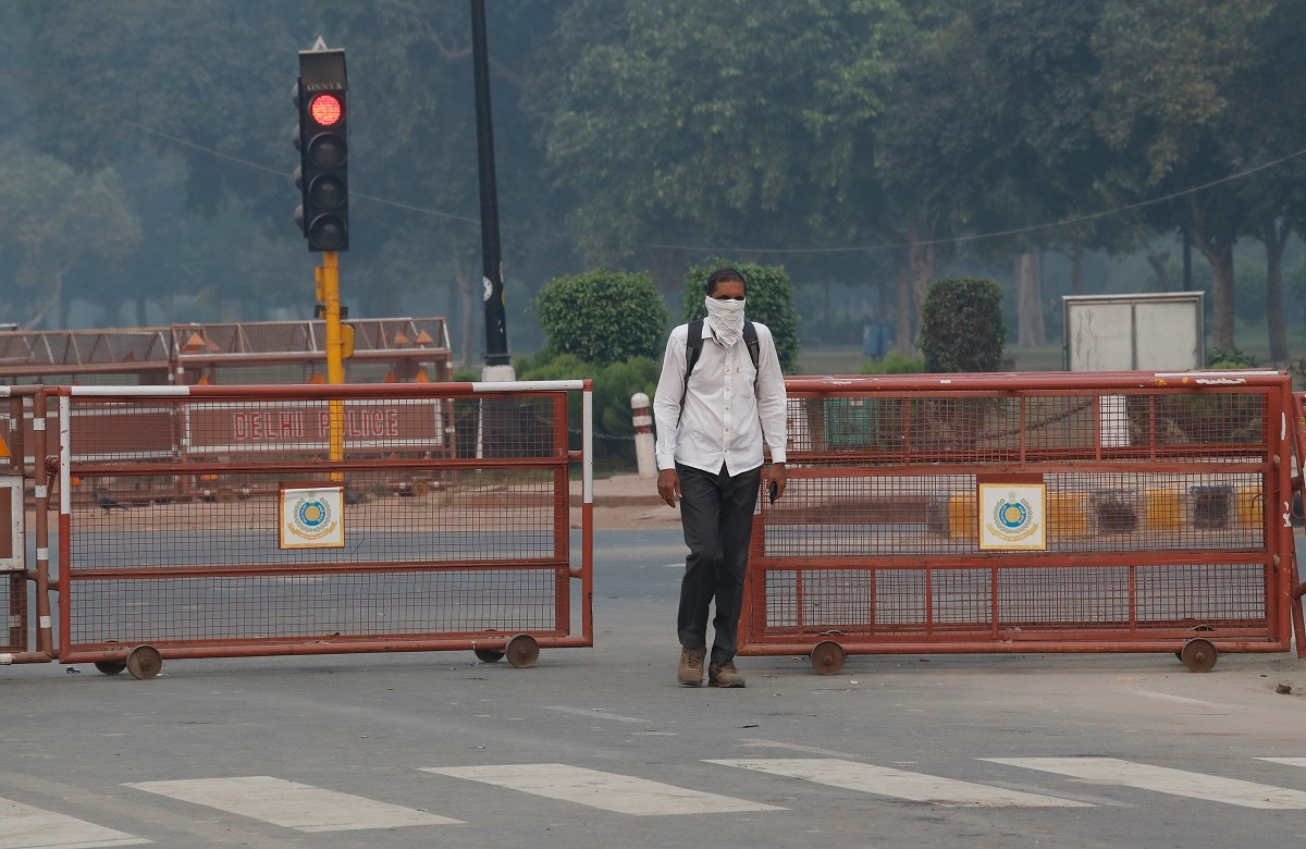 A man covers his face with a handkerchief as he walks to work early Monday morning. Due to emission from firecrackers and stubble burning in adjoining areas of the NCR, the pollution situation is expected to worsen in the coming weeks. (AP Photo/Manish Swarup)