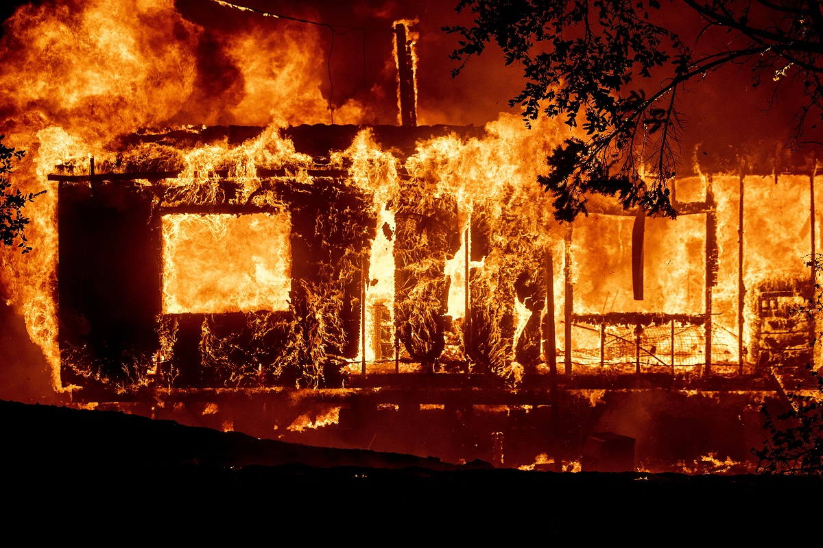 A wildfire on Los Angeles' wealthy west side destroyed several homes and forced thousands to flee early Monday, while a blaze in Northern California wine country exploded in size. (AP Photo/Noah Berger)