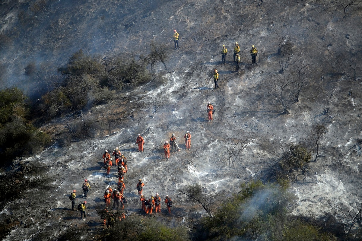 Hand crews work a wildfire-damaged hillside as the Getty fire burns on Mandeville Canyon in Los Angeles. (AP Photo/Marcio Jose Sanchez)