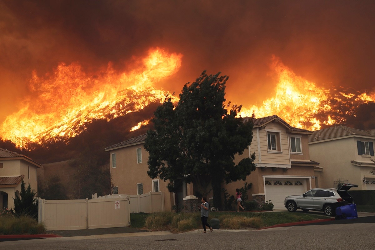 The flames that roared up a hillside near the J. Paul Getty Museum in Los Angeles' Brentwood section illustrated the unprecedented danger the state faces as high winds batter both ends of California. (AP Photo/Marcio Jose Sanchez)