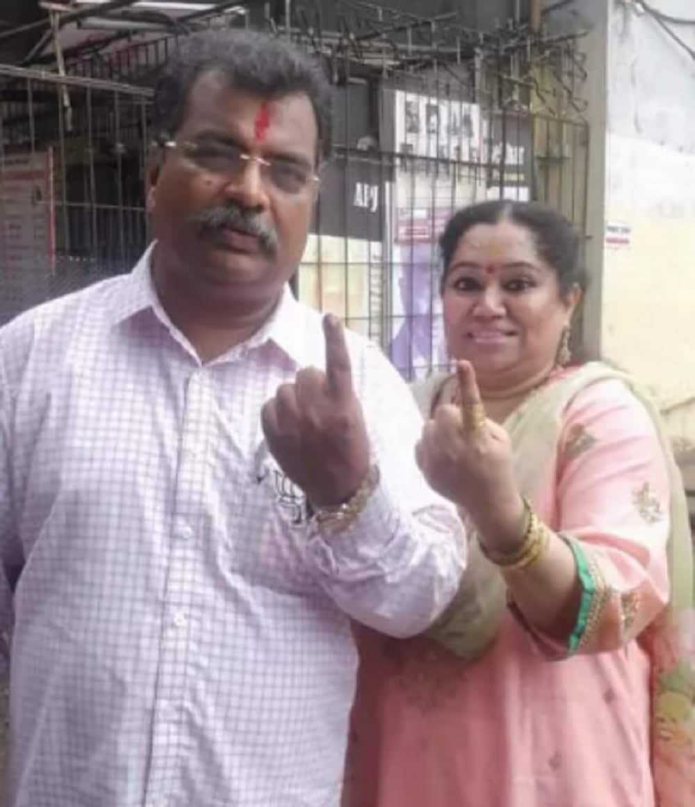 BJP minister and candidate Ravindra Chavan with his wife show their fingers marked with indelible ink after casting vote. (Image: News18)