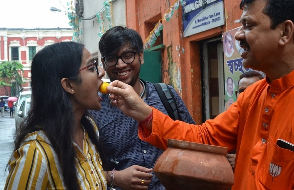 BJP workers distribute sweets in Kolkata following the saffron party's performance in assembly elections. (Photo: IANS)