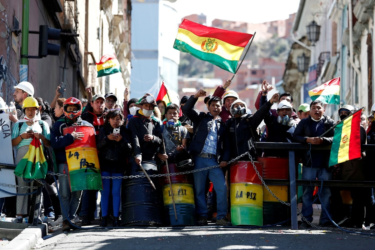People shout slogans during a protest against Bolivia's President Evo Morales in La Paz, Bolivia. President Evo Morales faced rising pressure to resolve a weeks-long standoff over Bolivia's disputed election on Saturday after police forces were seen joining anti-government protests and the military said it would not