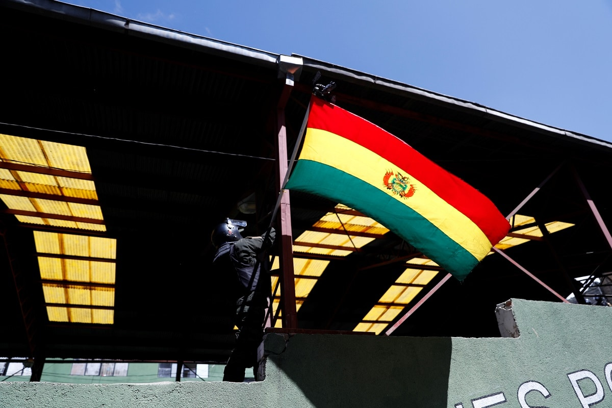 An officer places a national flag in a police station during a protest against Bolivia's President Evo Morales in La Paz, Bolivia. Morales, Latin America's longest-standing leader, won an election on October 20, but a delay of nearly a day in the vote count sparked allegations of fraud and led to protests, strikes and roadblocks. REUTERS/Carlos Garcia Rawlins