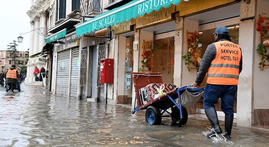 A hotel porter pushes a cart with luggage through water during high tide in Venice, Italy November 17, 2019. REUTERS/Alberto Lingria