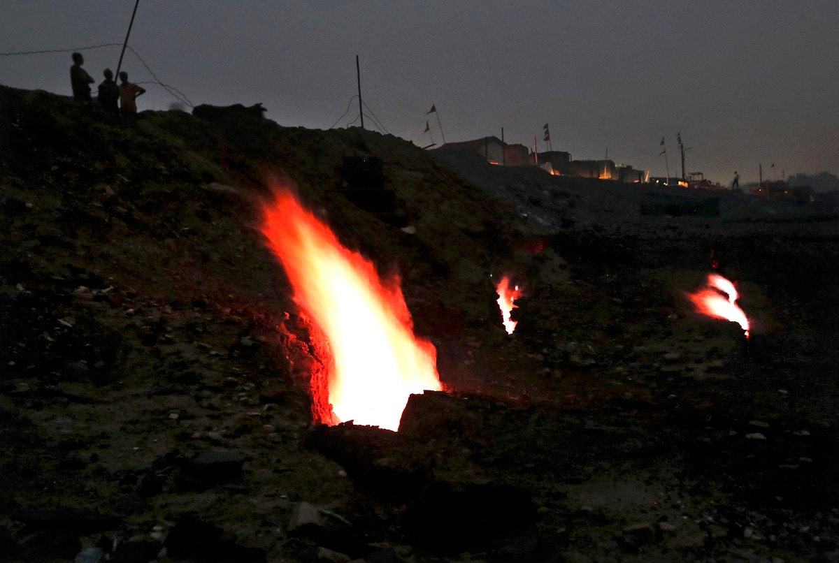 Flames billow out of the fissures on the ground above coal mines in the village of Liloripathra in Jharia. (AP Photo/Aijaz Rahi)