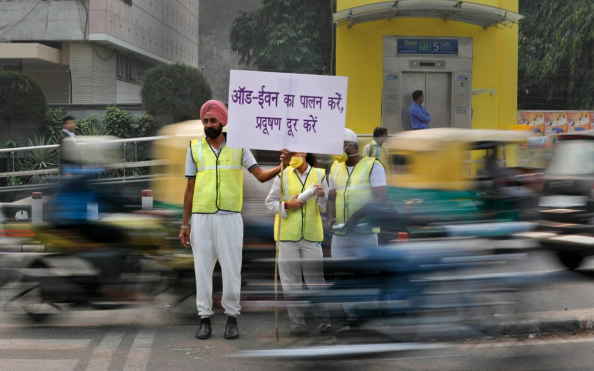 Volunteers wear pollution masks as they stand at a busy crossing with the banner saying