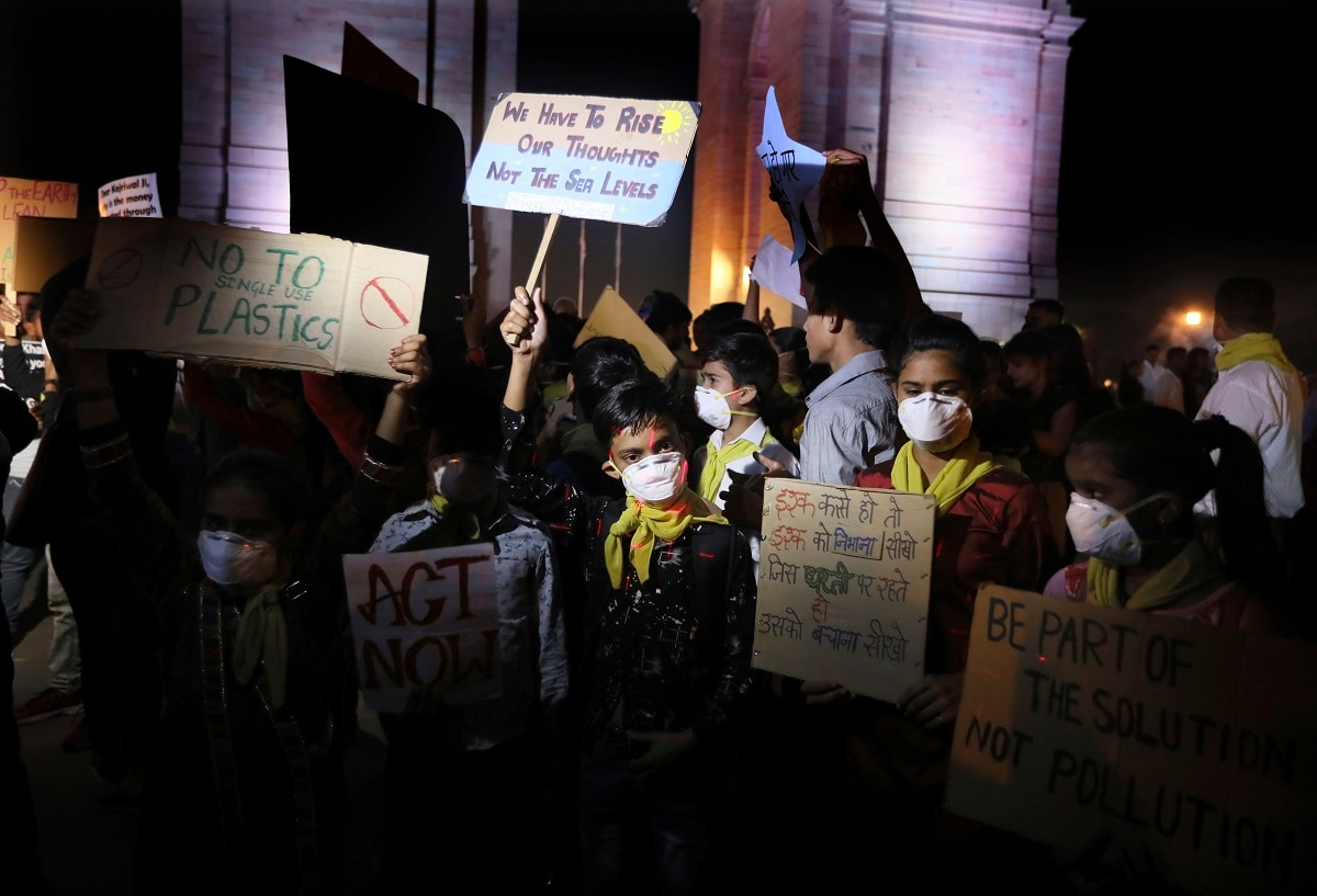 Children wear masks and hold placards during a protest against the alarming levels of pollution in the city, near the India Gate. (AP Photo/Manish Swarup)