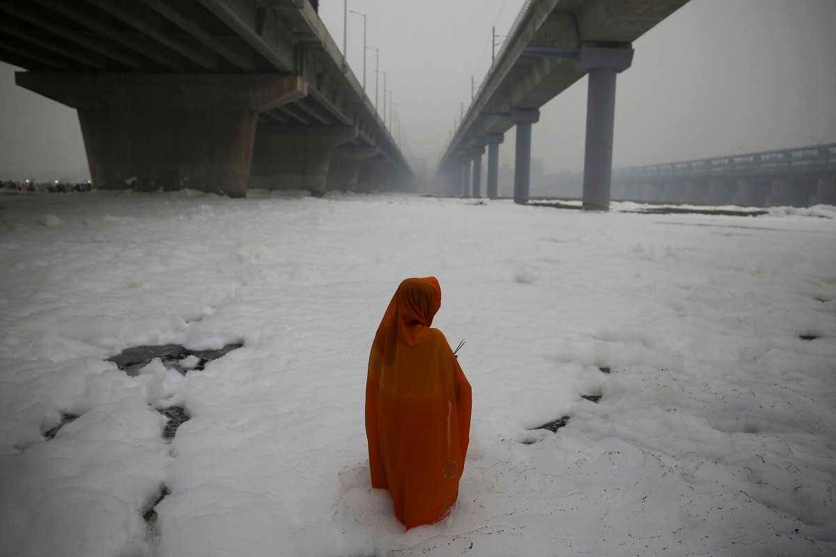 A devotee performs rituals in the Yamuna river, covered with chemical foam. Authorities are tackling a large amount of toxic foam floating in the Yamuna River, caused partly by high ammonia levels emanating from industrial pollutants. (AP Photo/Altaf Qadri, File)