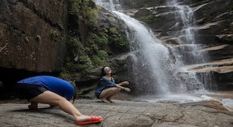 A woman poses for photos near a waterfall in Wuyishan in eastern China's Fujian province on Thursday, Aug. 15, 2019. (AP Photo/Ng Han Guan)