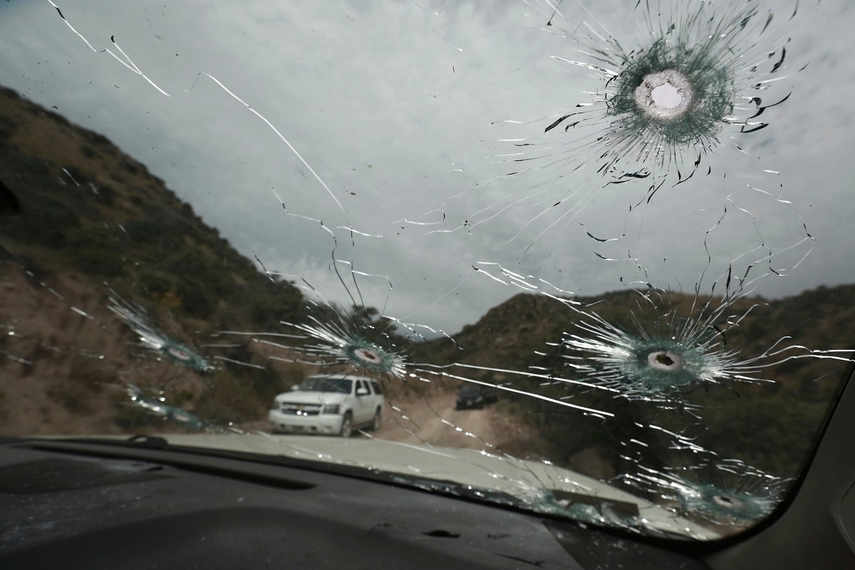 Bullet-riddled vehicles that members of the extended LeBaron family were travelling in sit parked on a dirt road near Bavispe, at the Sonora-Chihuahua state border, Mexico. Three women and six of their children, related to the extended LeBaron family, were gunned down in an attack while travelling here Monday. (AP Photo/Christian Chavez)