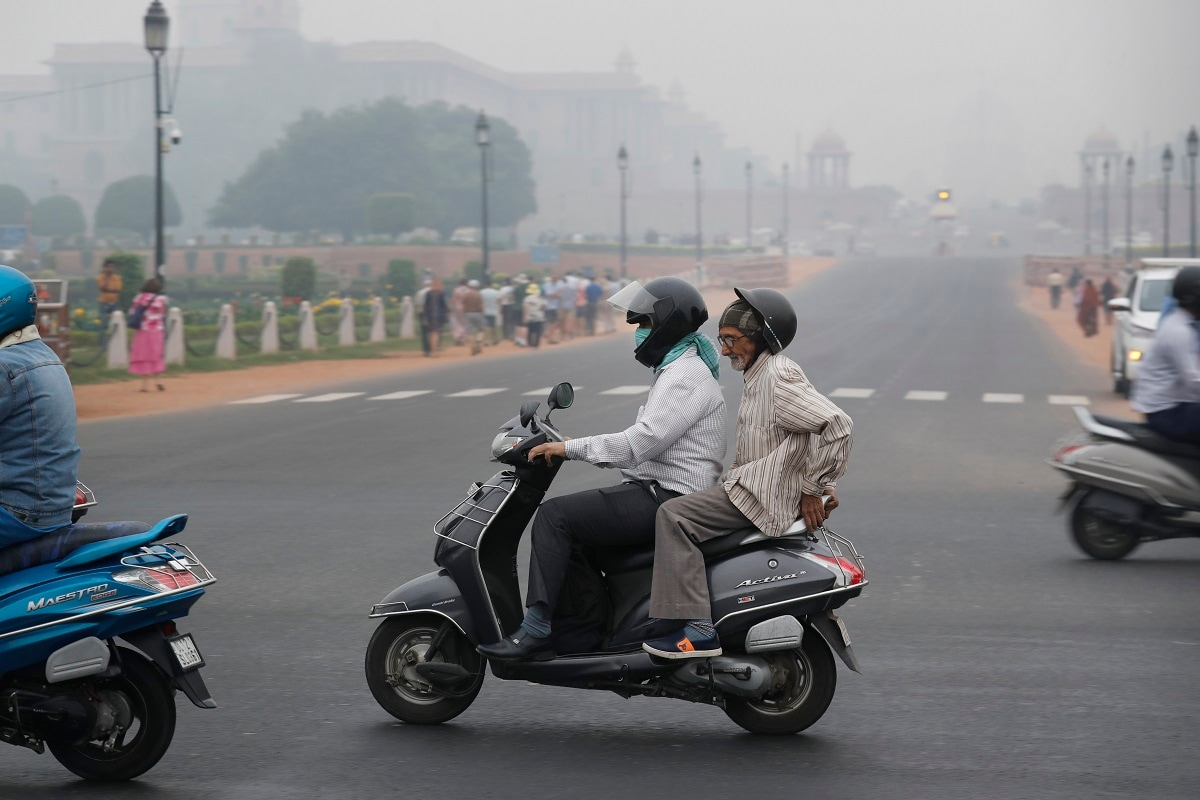A man covers his face with a cloth and drives amidst smog in New Delhi. (AP Photo/Manish Swarup)