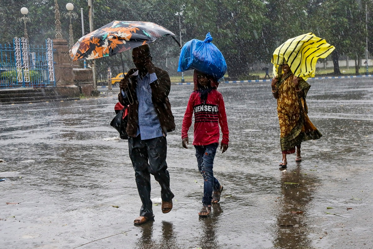 People walk in the rain in Kolkata. Authorities in nearby Bangladesh put more than 50,000 volunteers on standby and readied about 5000 shelters as a strong cyclone in the Bay of Bengal is expected to hit the low-lying nation's vast southwestern and southern coast on Saturday evening. (AP Photo/Bikas Das)