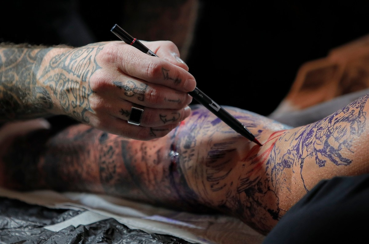 A tattoo artist pains the base of a tattoo on a man's leg during the 10th International Tattoo Convention in Bucharest, Romania. (AP Photo/Vadim Ghirda)